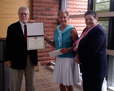 Pat, center, accepts her Norman Mailer CICC Writing Award